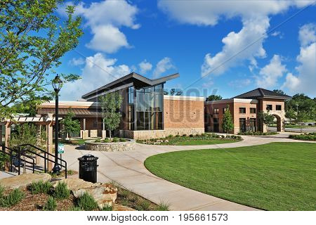 Generic Brick And Glass Office retail Building exterior with v shaped roof and interesting landscaping