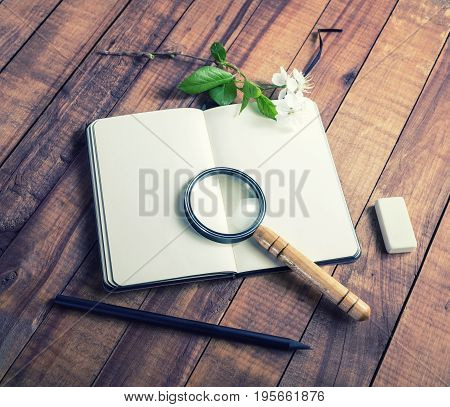 Blank notebook magnifier flowers and green leaves on vintage wood background. Template for placing your design. Responsive design mockup. Stationery elements.