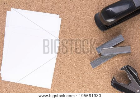 Note paper with staples and a stapler on a cork board