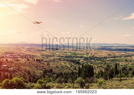 Panorama of the suburbs of the Greek city of Athens with landing plane at sunset