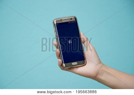 Bangkok Thailand July 8 2017 : Woman held android smart phone Samsung galaxy S7 Edge with facebook application screen on blue concrete background.