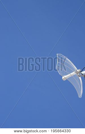 Vertical shot of a wireless internet antenna reciever against blue sky with loads of cop-space