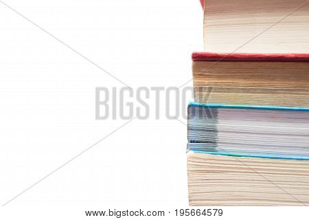 Close-up of stacked used books isolated on white with copy-space on the left