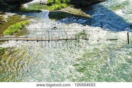 mountain river with a rapid current of clean water and an old outboard broken bridge