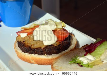 Hamburger with grilled meat on a plate. Fast food.