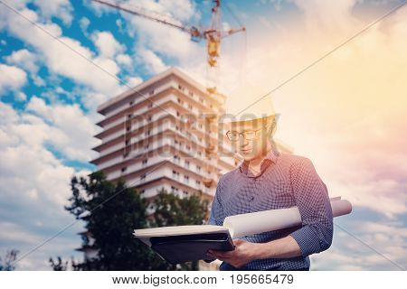 Male construction builder worker - foreman is an engineer in a protective helmet, glasses on the background of building a house with a crane. Concept business.