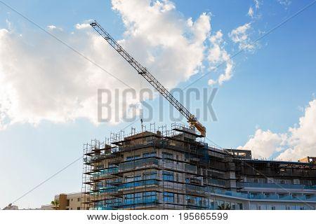 Building crane and building under construction against blue sky.