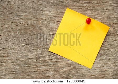 Yellow paper pin on brown wood background for memo notice or to do list