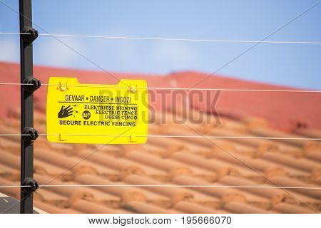 Secure electric fencing installed on residential wall and a blurred roof of a house in the background with yellow danger sign that warns about elecrical shock in Afrikaans English and IsiXhoza languages