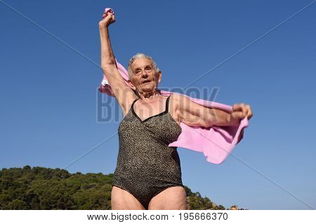 Older Woman Wiping Skin After Taking A Bath In The Sea