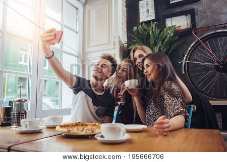 A guy taking a self-portrait with his female groupmates using his smartphone while hanging out in a coffee shop.