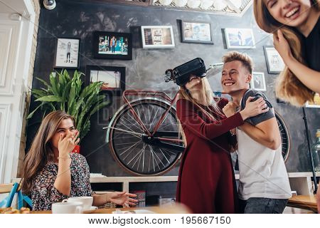Group of friends playing horror games in virtual reality goggles having fun and laughing loudly in loft apartment.