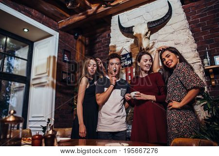 Group of young people posing at camera standing, smiling, laughing, making faces while having fun in trendy restaurant.