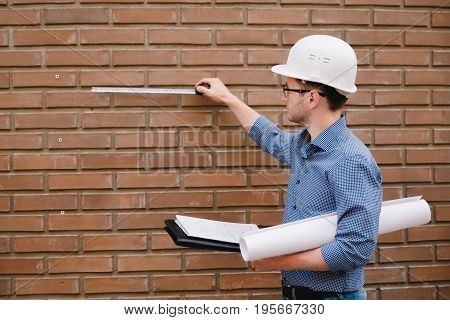 Male construction builder worker - foreman iengineer in a protective helmet, glasses on the background Brick wall ruler measures.Concept calculation copyspace