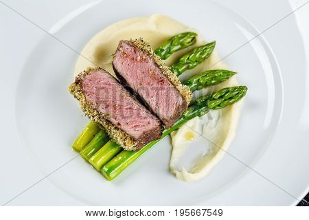 medium done grilled tuna steak with asparagus served on the asparagus and mashpotato