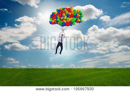 Businessman flying balloons on bright day