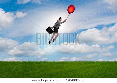 Businesswoman flying balloons on bright day