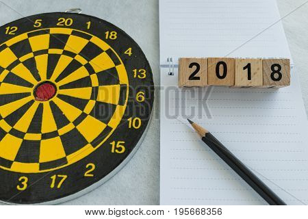 2018 goals and target concept with wooden blocks number and dartboard with note paper and pencil.