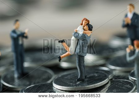 Miniature figure couple people standing on top stack of coins and other clapping as success love life concept.