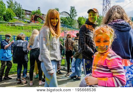 Moscow, Russia - June 3, 2017: A little girl, stained with orange paint on background of other participants festival of colours Holi. Summer celebration Holi has turned into fun event in many cultures