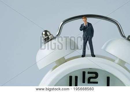 business or time countdown concept as miniature thinking businessman figure standing on white alarm clock.