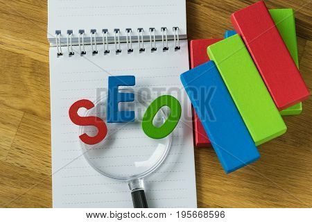 SEO concept as colorful alphabet abbreviation on magnifying glass on note paper and wooden block as analysis chart on wooden table.
