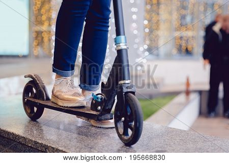 girl in blue pants is standing on a scooter, on a blurred city background. Concept of mobile urban youth transport.