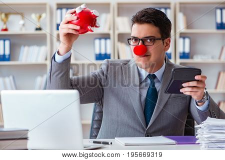 Clown businessman with piggy bank doing accounting