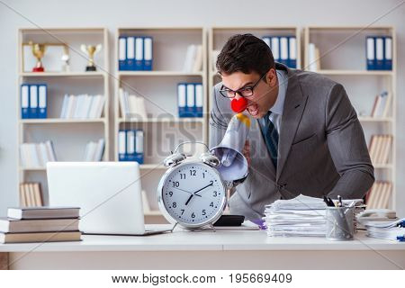 Clown businessman in the office angry frustrated with megaphone