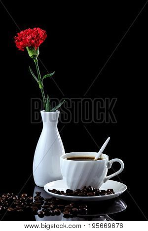 Composition Of Coffee And Red Carnation On A Black Reflective Background. Studio Shot