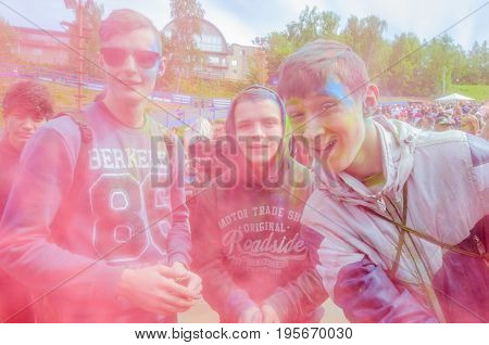 Moscow, Russia - June 3, 2017: Group portrait of joyfully laughing and smiling three teenage boys in cloud of pink dust at festival of colours Holi. Epicenter of colorful explosion of Holi-expression