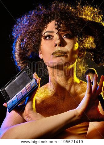 Woman with decorative cosmetics. Girl with curls holds eye shadow and brush on dark background. Golden powder on female bare shoulders. Creation of stage image by dint of professional makeup.