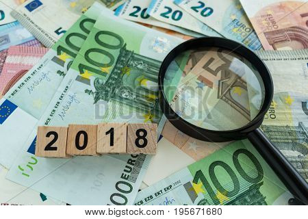 financial tax concept as magnifying glass on pile of euro banknotes and number 2018 on wooden block.