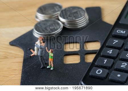 Miniature happy family figure standing on paper house with calculator as mortgage or financial investment plan concept.