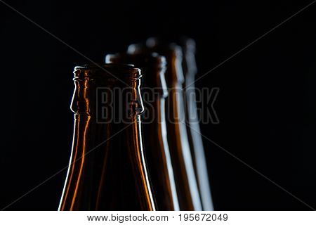 Silhouettes brown glass bottles for beer on a black background