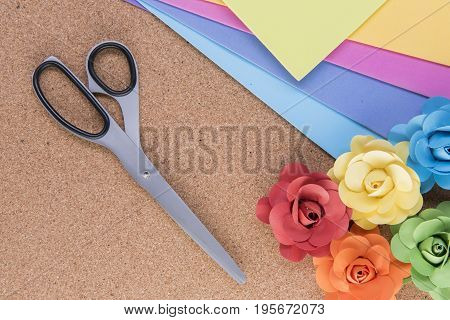 Colourful paper craft background with paper, scissors and paper roses