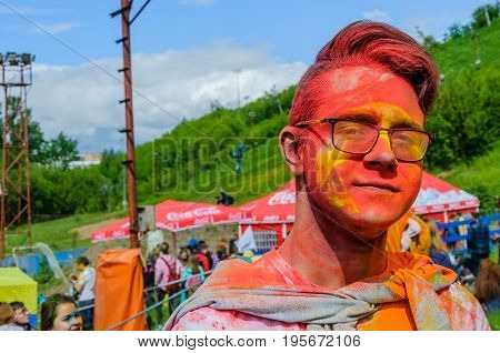 Moscow, Russia - June 3, 2017: Closeup portrait of stylish teenager wearing glasses with face in red paint after Holi-expression battle. Summer celebration Holi turned into fun event in many countries
