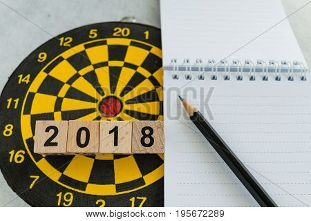 Year planning target or goals concept with wooden blocks number 2018 on dartboard and pencil with note paper.