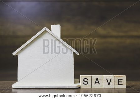 House model with save word on wooden blocks. Home finance concept