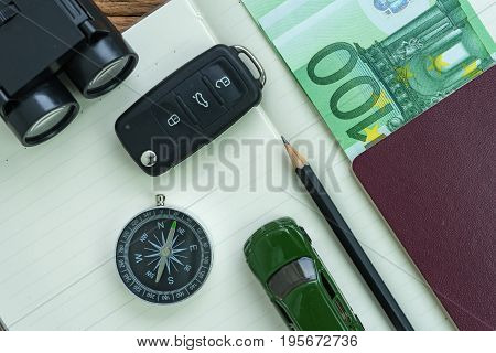 car key compass pencil with passport euro banknote on paper note and miniature car as travel planning road trip concept.