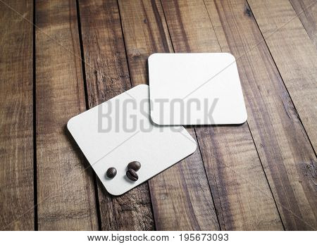 Blank square beer coasters and coffee beans on vintage wooden table background. Responsive design mockup.