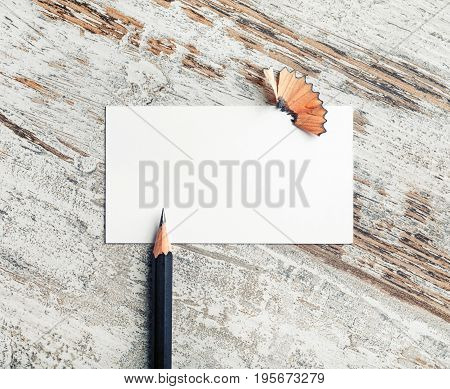 Blank business card and pencil on vintage wooden background. Stationery and ID mock up. Top view.