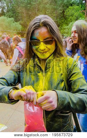 Moscow, Russia - June 3, 2017: Girl, smeared with yellow paint during expressive Holi-battle open pack with pink powder. Traditional summer Indian festival Holi turned into fun event in many countries