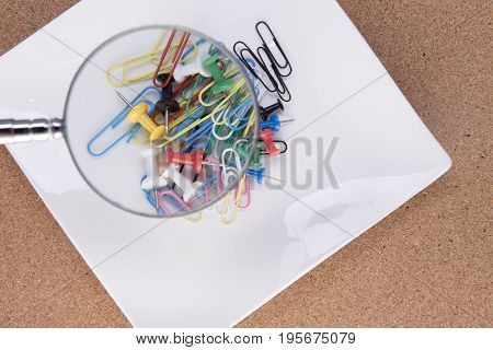 Background image of a magnifying glass over colourful paperclips and drawing pins on a white plate