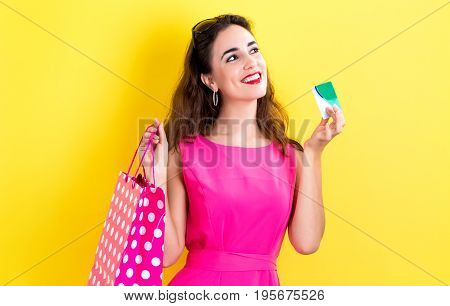 Young woman holding a credit card and a shopping bag