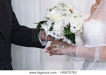 Bride and groom with wedding bouquet of white flowers in their hands, groom gives a bouquet to bride, closeup view