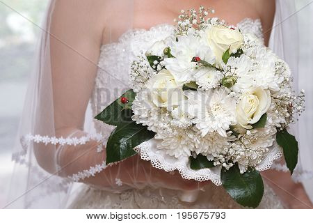 Wedding bouquet of white flowers in bride's hand, closeup
