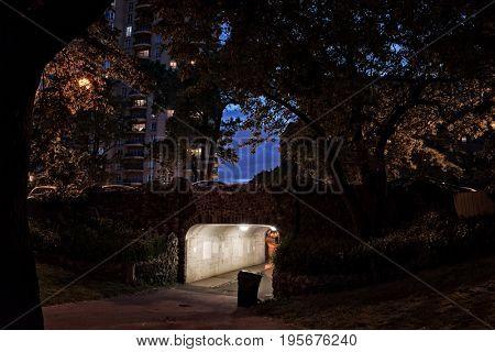 Dark urban downtown bridge with underpass and sidewalk at night.