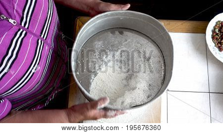 Sifting the Flour Through a Hand Sieve.