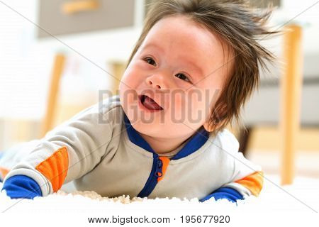 Happy smiling baby boy crawling in his house